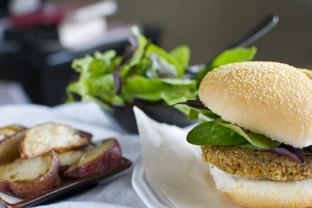 A delicious vegan burger made with black beans and chickpeas is served with potato wedges and a salad.